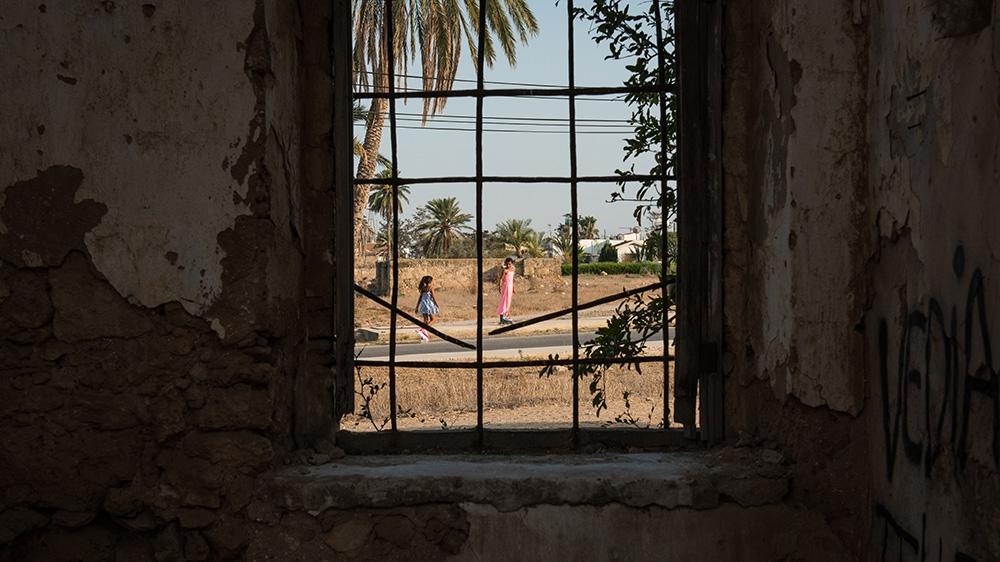 Children playing on the street can be seen through the window of a deserted church in Famagusta [Wojtek Arciszewski/Al Jazeera]